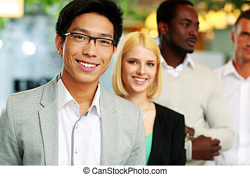 Portrait of a smiling asian businessman standing in front of...