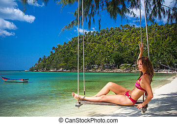 Young woman swings on a tropical beach. Thailand