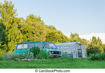 mini bus parked next to village greenhouse in yard - old...