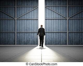 Man walks to large hangar doors - Man walks into light of...