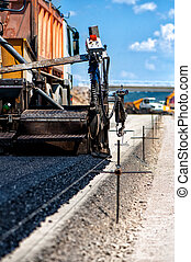 Industrial pavement truck or machine laying fresh bitumen...