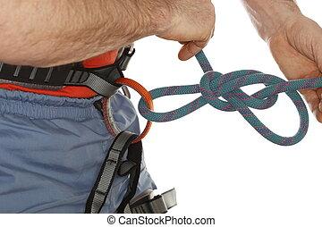 bind - sport climber is binding a knot on belt