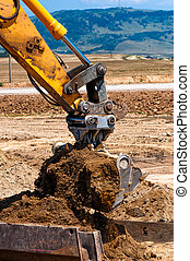 heavy duty construction excavator loading sand into a dumper...
