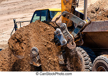 Close-up of heavy duty excavator truck loading sand on...