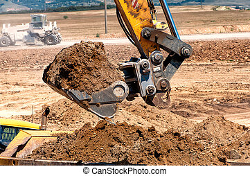 Close-up of heavy duty excavator scooping into earth and...