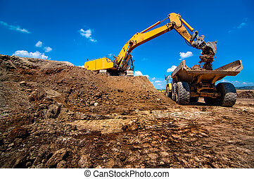 Industrial excavator loading soil material from highway...