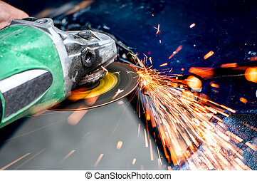 Heavy industry worker cutting steel with angle grinder in...