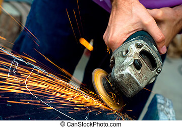 Heavy industry worker cutting steel with angle grinder at...