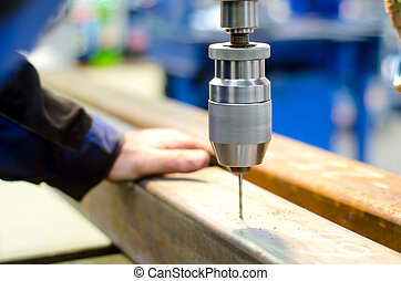 industrial worker drilling a hole with automatic drill machine