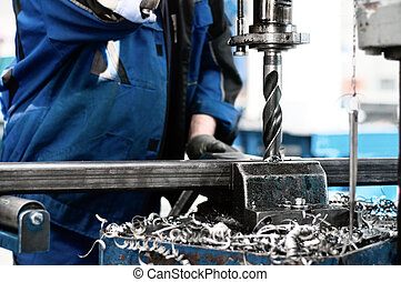 industrial tehnician working on a drilling machine - making...