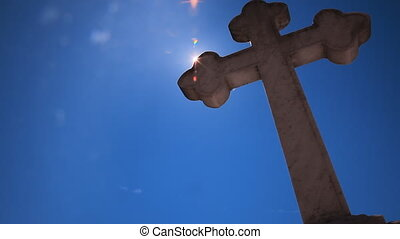 cross blue sky sun rays - historic cross seen from low angle...