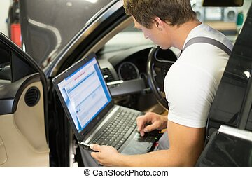 Serviceman making car diagnostics with laptop in a workshop