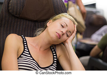 Lady traveling napping on a train. - Blonde casual caucasian...
