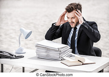 No more paperwork Frustrated young businessman holding head...