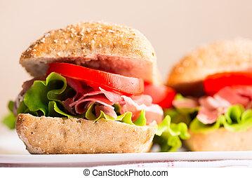 Prosciutto sandwich with tomato and arugula on plate