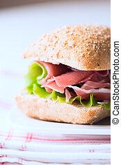 Prosciutto sandwich on plate macro vertical