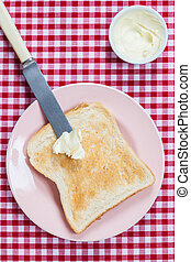 A golden brown slice of toast on a pink plate with butter