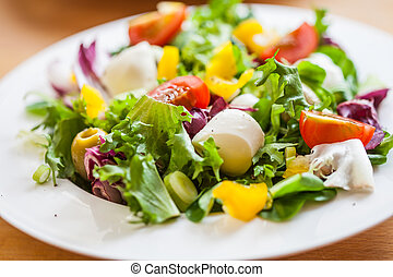 Two bowls of delicious fresh salad with mozzarella and pepper