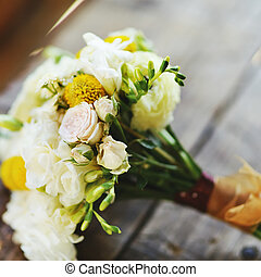 bridal bouquet with roses and freesia on a wooden surface