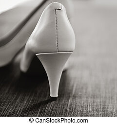 bridal shoes on a floor in black and white