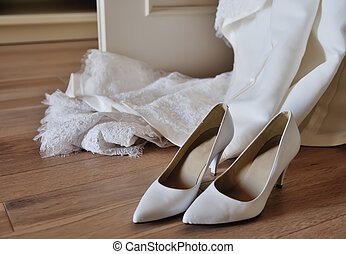 bridal shoes on a floor and hanging dress