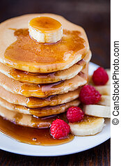 Delicious pile of hot homemade pancakes with fresh raspberries