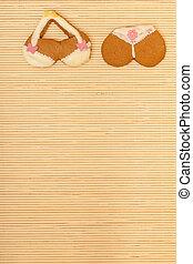Yellow pink bikini shape gingerbread cake cookie on bamboo...