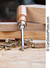 Phillips head screwdriver and wood screws - Close up view of...