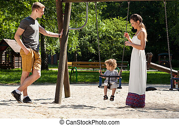 Family on playground - Mom, dad and little boy on playground