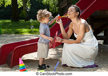 Mom and boy making bubbles - Mom and little boy making soap...