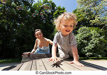 Boy and mum playing with bubbles - Little boy and mum...