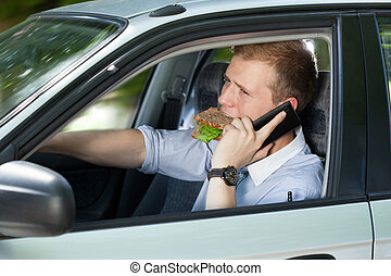 Busy man driving a car and talking phone