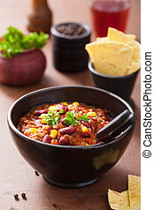mexican chili con carne in black plate with ingredients