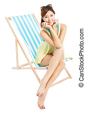 young woman smiling and sitting on a beach chair