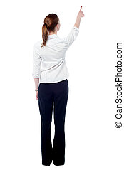 Young business woman pointing at wall