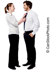 Pretty woman adjusting her husbands tie - Young woman...