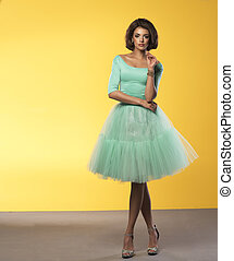Beauty young woman in retro turquoise dress on yellow...