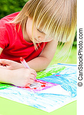Child drawing - Little girl sitting at table drawing a house...