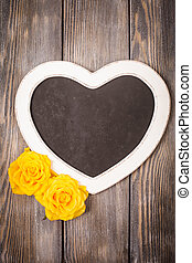 Heart shape chalkboard and yellow roses over wooden...