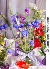 Wildflowers in bottles in the box. Kitchen flowers decor