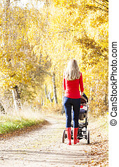 woman with a pram on walk in autumnal alley