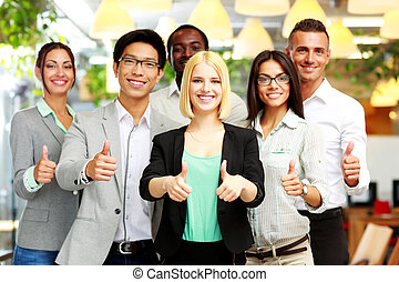 Smiling business group giving thumbs up