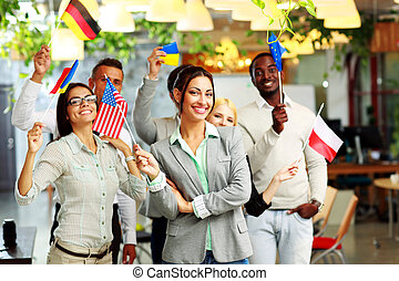 Happy group of businesspeople standing with flags in office