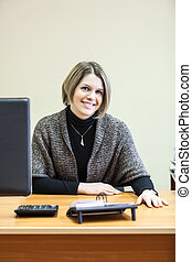 Smiling woman at the desc with computer monitor