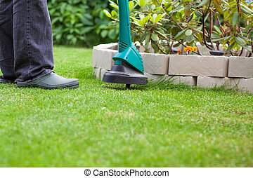 man mowing lawn with grass trimmer - man mowing lawn with...