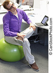 occupational disease prevention - man on stability ball...