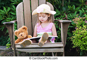 girl pretending to read - Little girl pretending to read to...