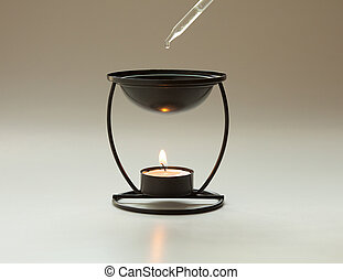 Aromatherapy burner - Essential oil being dropped into an...