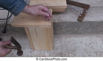hammering new wooden bird house nesting-box