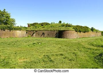 walls on green dry moat of Cittadella, Alessandria, Italy -...